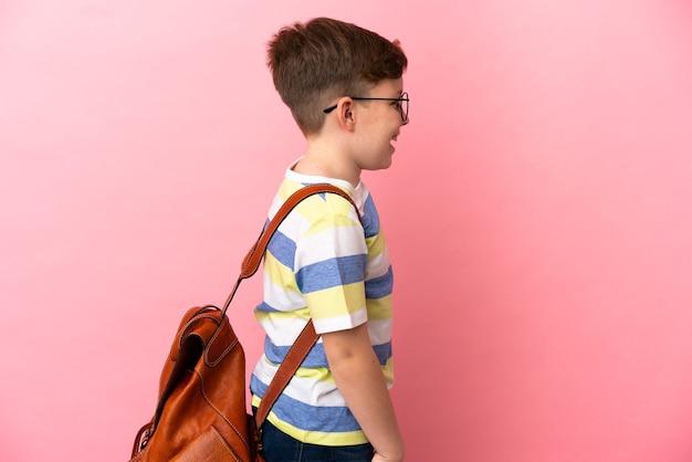 Маленький рыжий кавказский мальчик, изолированные на розовом фоне, смеясь в боковом положении