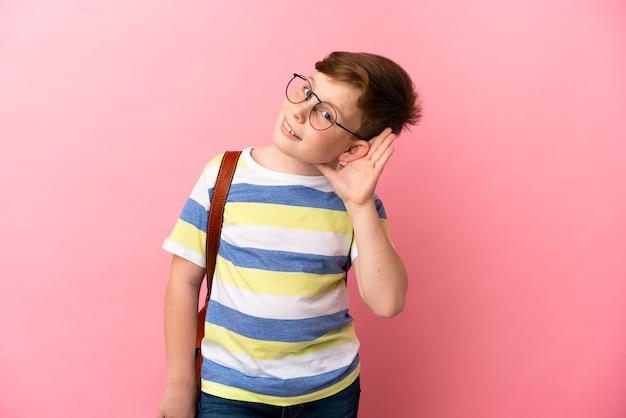 귀에 손을 대고 뭔가를 듣고 분홍색 배경에 고립 된 작은 빨간 머리 백인 소년