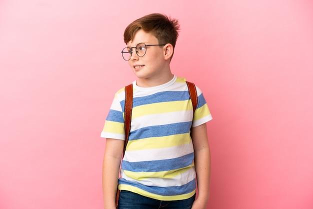분홍색 배경에 격리된 작은 빨간 머리 백인 소년은 옆을 바라보며 웃고 있다