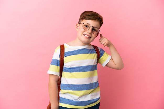 電話のジェスチャーを作るピンクの背景に分離された小さな赤毛の白人の少年。コールバックサイン