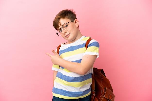 Маленький рыжий кавказский мальчик, изолированные на розовом фоне, указывая назад