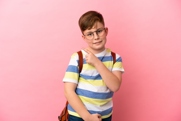제품을 제시하기 위해 측면을 가리키는 분홍색 배경에 고립 된 작은 빨간 머리 백인 소년