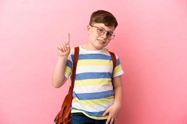 좋은 아이디어를 가리키는 분홍색 배경에 고립 된 작은 빨간 머리 백인 소년