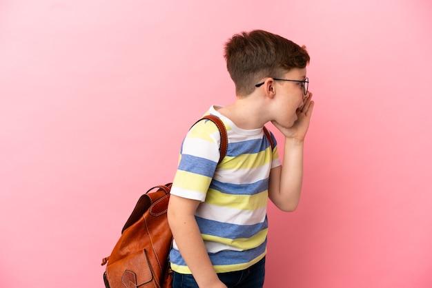 Маленький рыжий кавказский мальчик изолирован на розовом фоне и кричит с широко открытым ртом в сторону