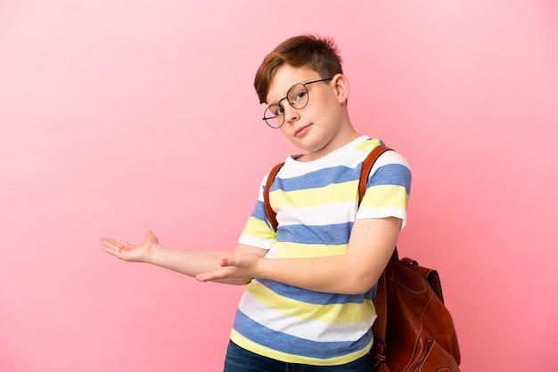 분홍색 배경에 격리된 작은 빨간 머리 백인 소년은 옆을 바라보면서 놀란 표정을 지었다
