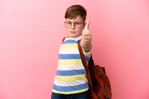 Маленький рыжий кавказский мальчик изолирован на розовом фоне с большими пальцами руки вверх, потому что произошло что-то хорошее