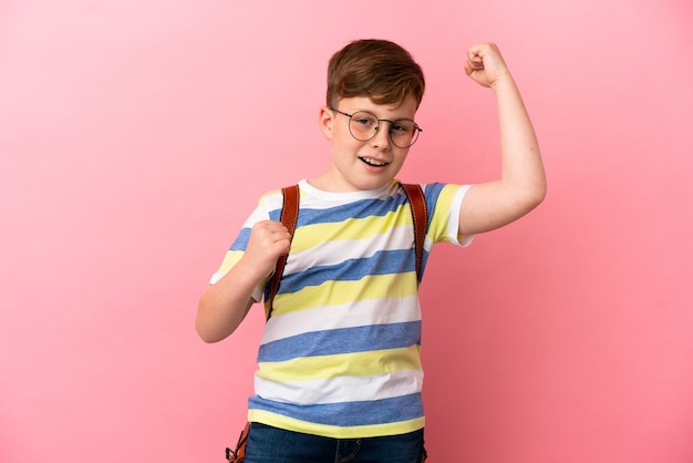 Little redhead caucasian boy isolated on pink background celebrating a victory