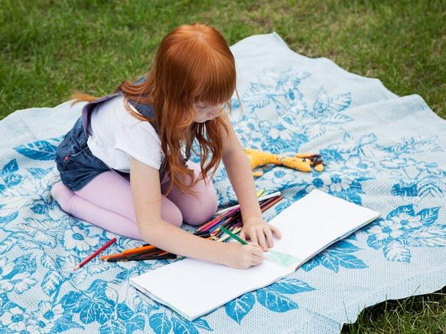 Маленькая рыжая девочка рисует карандашами на пледе на лужайке