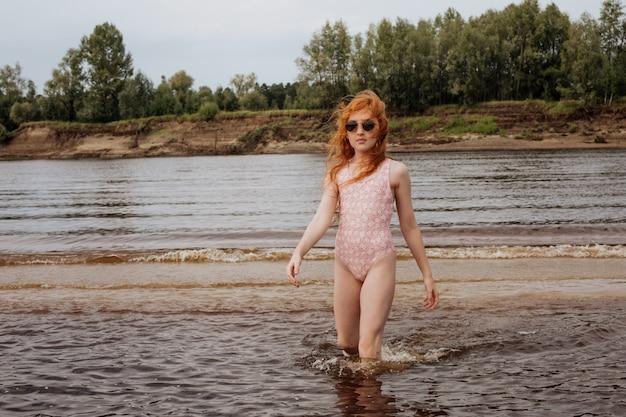 Маленькая рыжая девочка играет на пляже