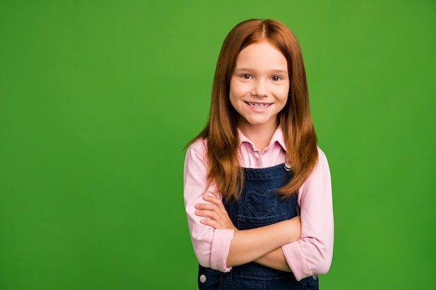 Little redhead girl posing against the green wall