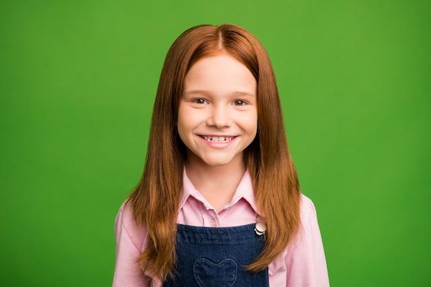Маленькая рыжая девушка позирует у зеленой стены