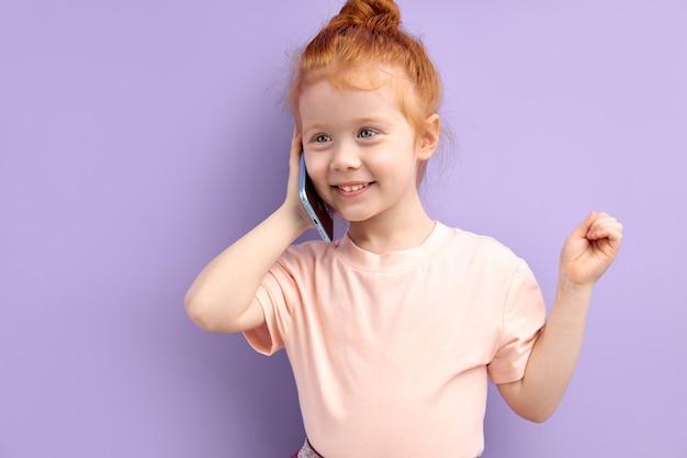 屋内で電話で話している小さな赤毛の女の子