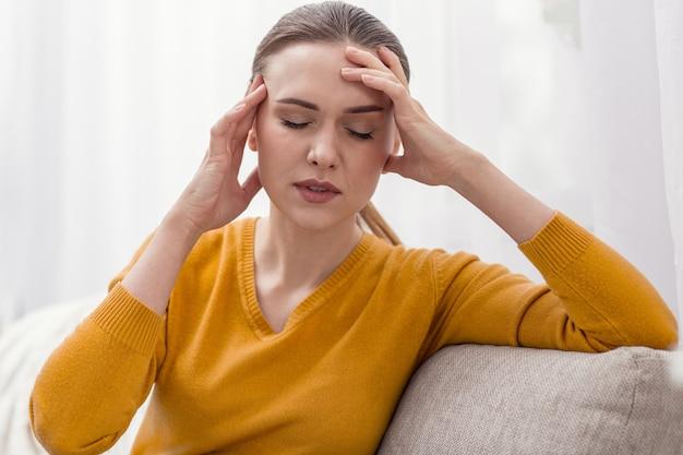 少し安心。ブルネットの愛らしいストレスの多い女性は、リラックスして目を閉じながら頭を愛撫します