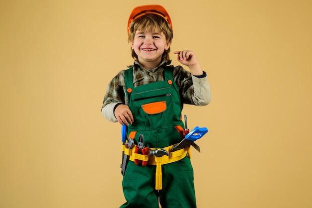 작은 수리공. 빌더 제복을 입은 꼬마 소년과 수리 도구가 있는 헬멧. 어린이 게임. 어린 소년 건설 노동자를 재생합니다.