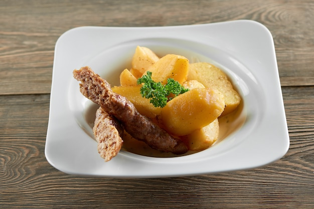 Little restaurant bowl served with goldy fried potato slices, thin sausage and decorated with parsley leaves. looks very delicious and nourisihing.