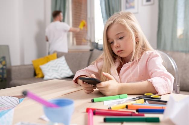 Маленькая спокойная белокурая девочка прокручивает в смартфоне, сидя за столом в гостиной с отцом, чистящим окна на заднем плане