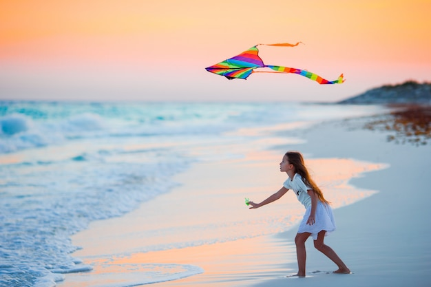Little running girl with flying kite on tropical beach at sunset. kids play on ocean shore. child with beach toys.