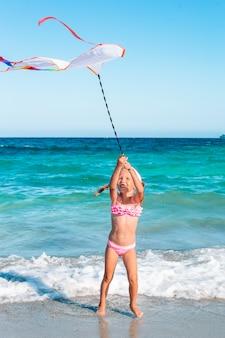 Little running girl with flying kite on tropical beach