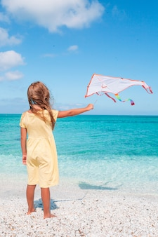 Little running girl with flying kite on tropical beach