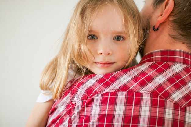 Little sad girl on dad's arms. daughter hugs dad.