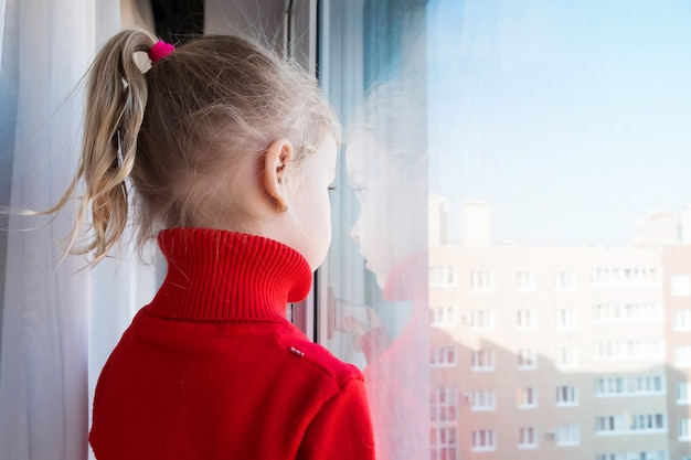 Little sad girl looking out of the window. stay at home quarantine. isolation concept. virus epidemic outbreak, healthcare medical crisis