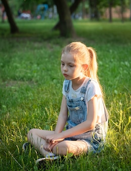 Little sad girl sitting in the park on the grass