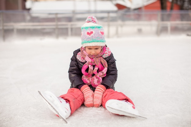 Little sad girl sitting on a skating rink after the fall