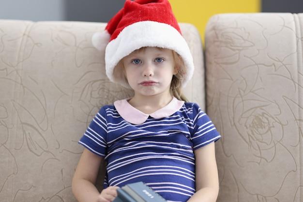 Little sad girl sitting on sofa wearing santa claus hat