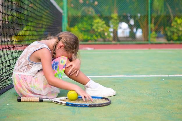 Little sad girl on tennis court