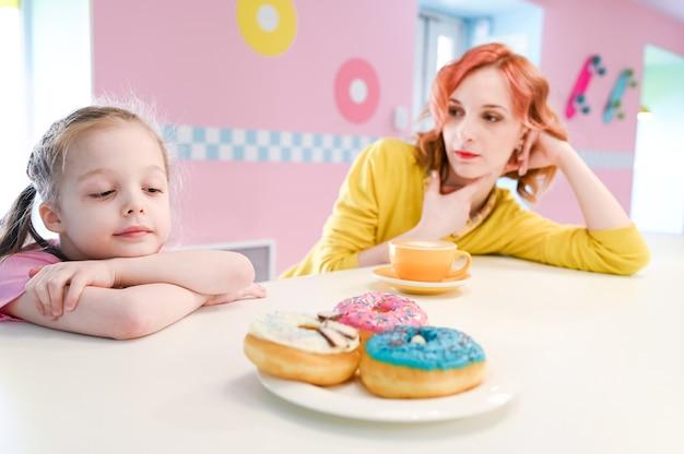 Маленькая грустная девочка смотрит на сладкие пончики в кафе. концепция диеты