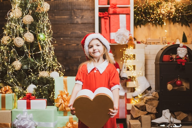 Little santa claus gifting gift winter christmas emotion home christmas atmosphere happy little girl...