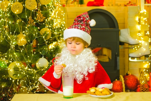 Little santa claus kid with beard and mustache santa funny child picking cookie portrait of little s...