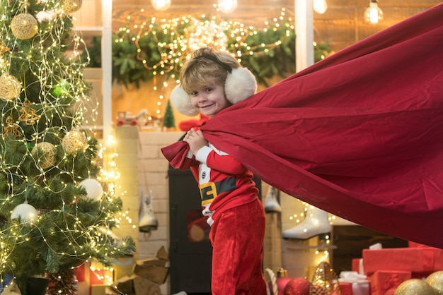 Little santa claus pulling huge bag of gifts on christmas background. santa helper carrying sack full of gifts. funny little santa claus with huge red bag with presents.