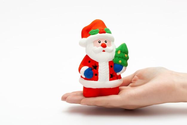 흰색 배경에 고립 된 여자의 손에 작은 산타 클로스 장난감. 크리스마스와 새해 개념