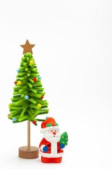 흰색 바탕에 장식 녹색 아름 다운 수 제 새 해 나무와 작은 산타 클로스 장난감. 크리스마스와 새 해 개념입니다. 디자인에 대 한 흰색 배경에 고립