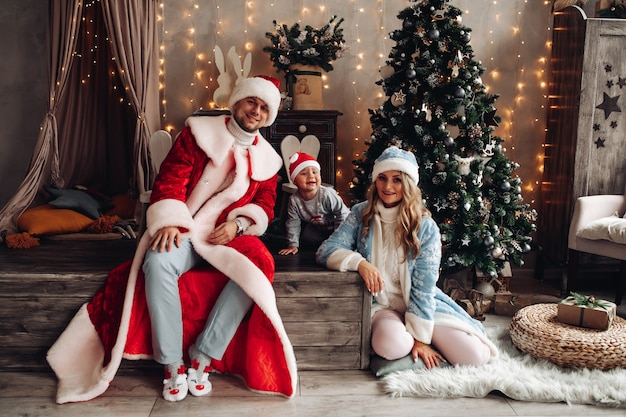 Little santa, father frost e snow maiden sorridente all'interno di natale con albero di natale decorato.