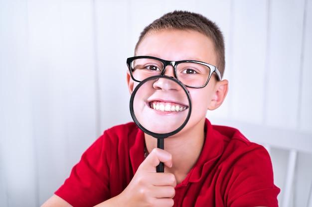 小さな男子生徒は虫眼鏡を通してポジティブな感情とネガティブな感情を表現します。学校へ戻る。感情を表現する方法を教育します。