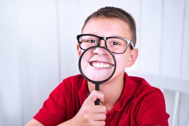 Little school boy express positive and negative emotions through a magnifying glass. go back to school. educat how to express feelings.