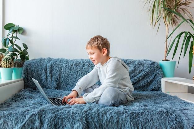 화상 통화, 노트북 e- 학습, 거리 공부, 거리 통신 개념에 온라인 수업을하는 어린 학교 소년