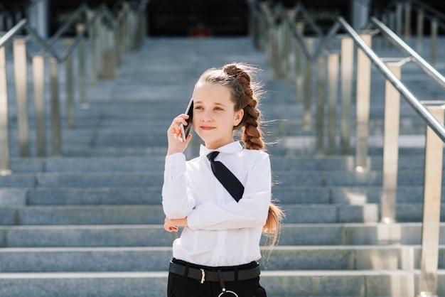 Little school girl having phone talk with friend