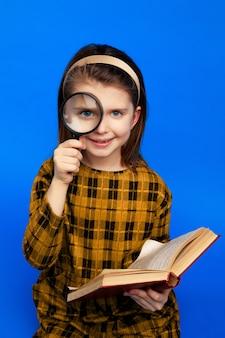 돋보기를 들고 웃 고 체크 무늬 드레스에 어린 학교 소녀