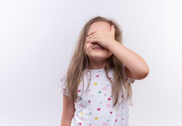 Маленькая школьница в белой футболке закрыла глаза рукой на изолированной белой стене