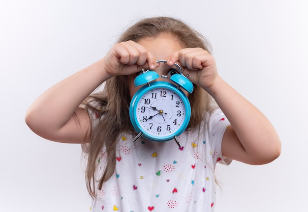 Little school girl wearing white t-shirt covered face with alarm clock on isolated white wall