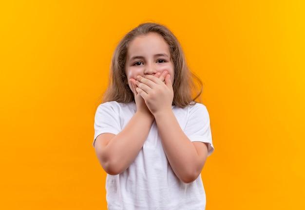 Piccola scuola ragazza che indossa t-shirt bianca coperta bocca con entrambe le mani sul muro arancione isolato