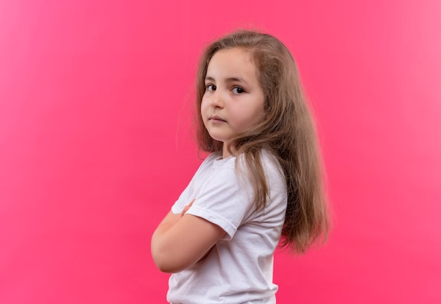 Little school girl wearing white t-shirt crossing hands on isolated pink wall
