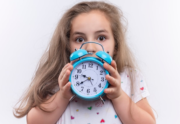 Little school girl wearing white t-shirt holding alarm clock on isolated white wall