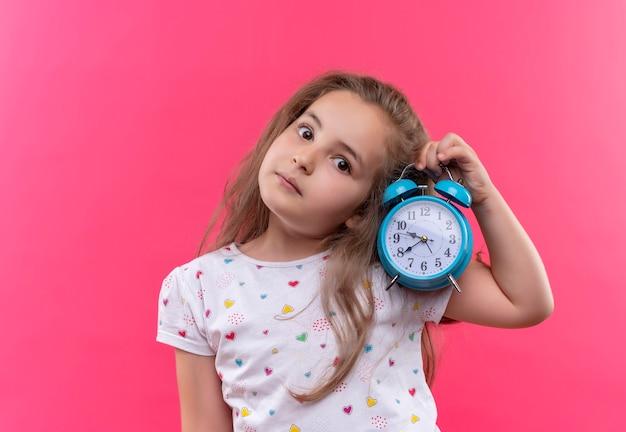 Piccola ragazza della scuola che indossa la maglietta bianca che tiene sveglia e ascolta sulla parete rosa isolata