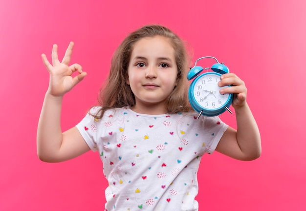 Little school girl wearing white t-shirt holding alarm clock showing okey gesture on isolated pink wall
