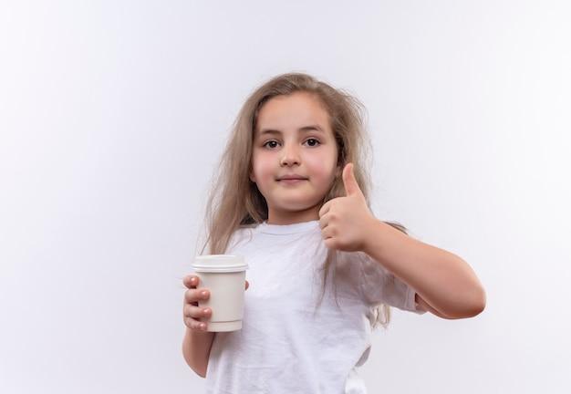 Piccola ragazza della scuola che indossa la maglietta bianca che tiene la tazza di caffè il suo pollice in su sulla parete bianca isolata