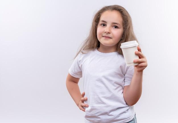 La piccola ragazza della scuola che indossa la maglietta bianca che tiene la tazza di caffè ha messo la sua mano sull'anca sulla parete bianca isolata